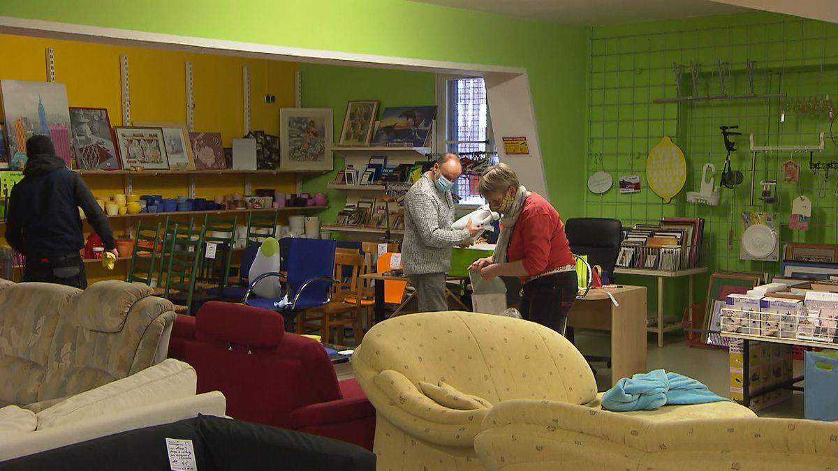 Mitarbeiter in einem Sozialkaufhaus mit Sofas und Stühlen.