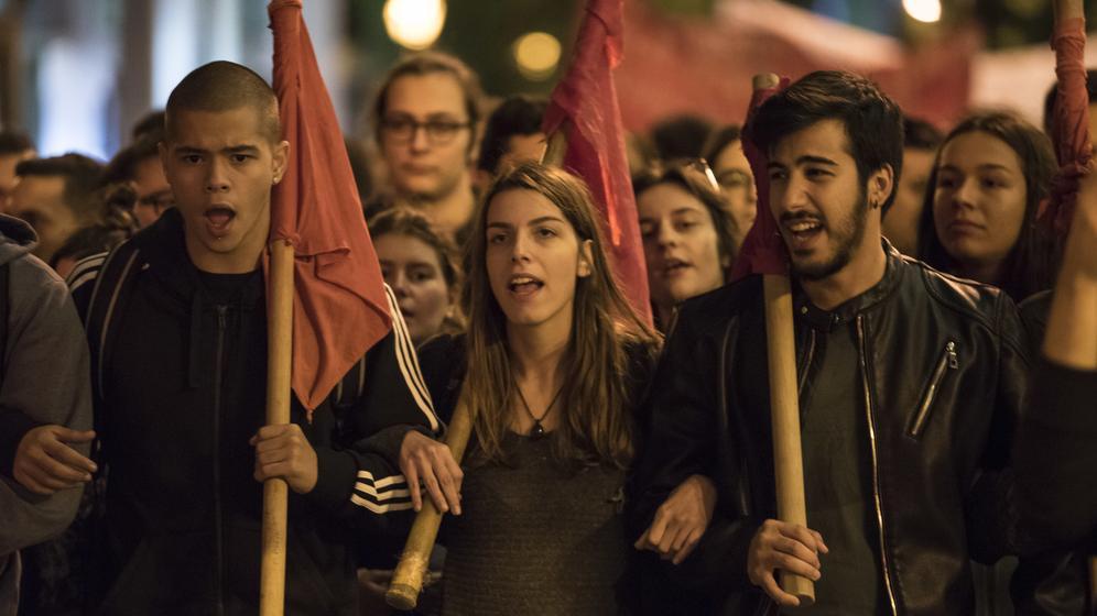 Junge Protestler marschieren mit roten Fahnen über der Schulter nebeneinander in Athen durch eine beleuchtete Straße | Bild:picture alliance/ZUMA Press