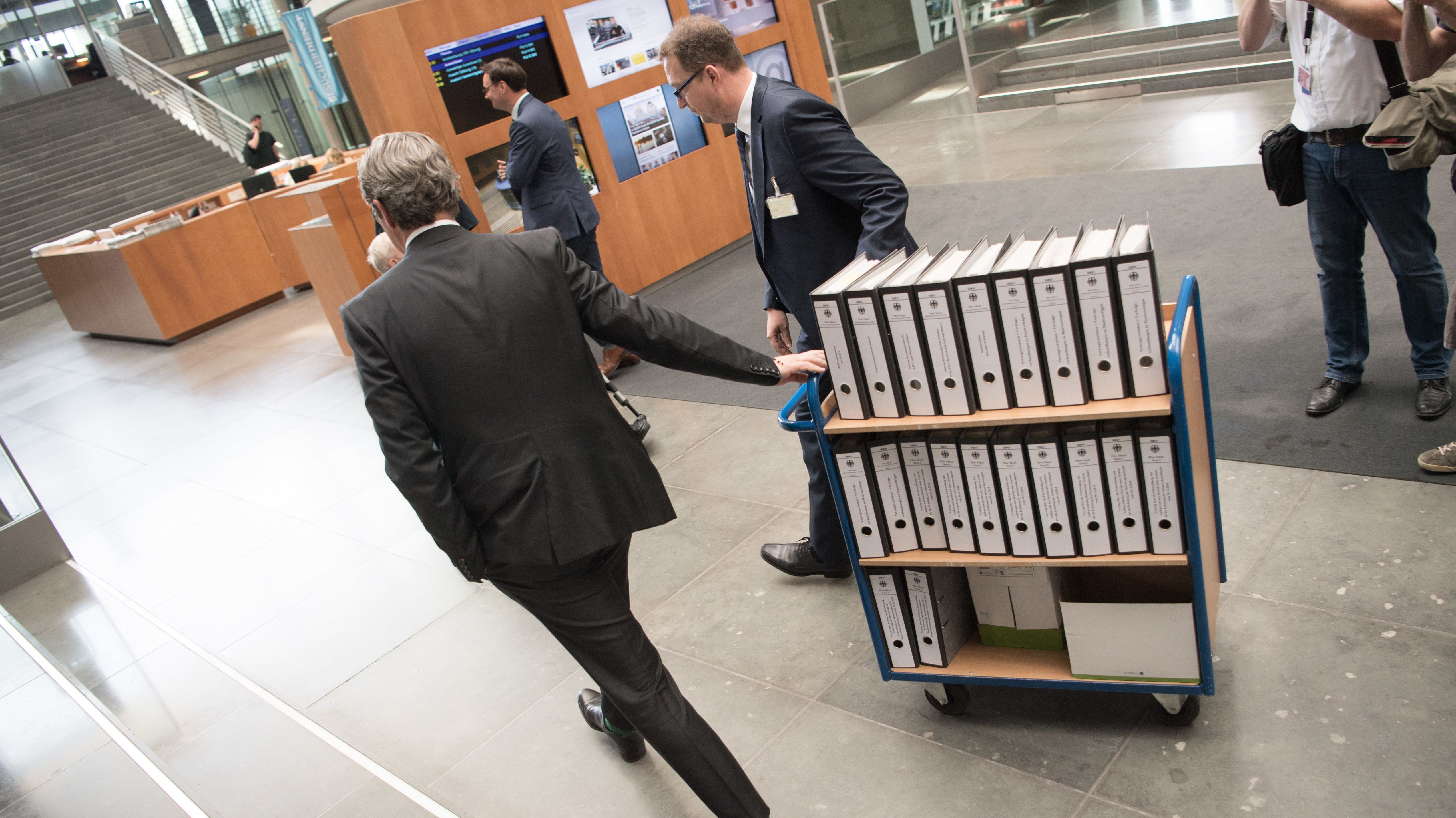 Bundesverkehrsminister Andreas Scheuer (links) mit Aktenordnern zur gescheiterten Pkw-Maut.