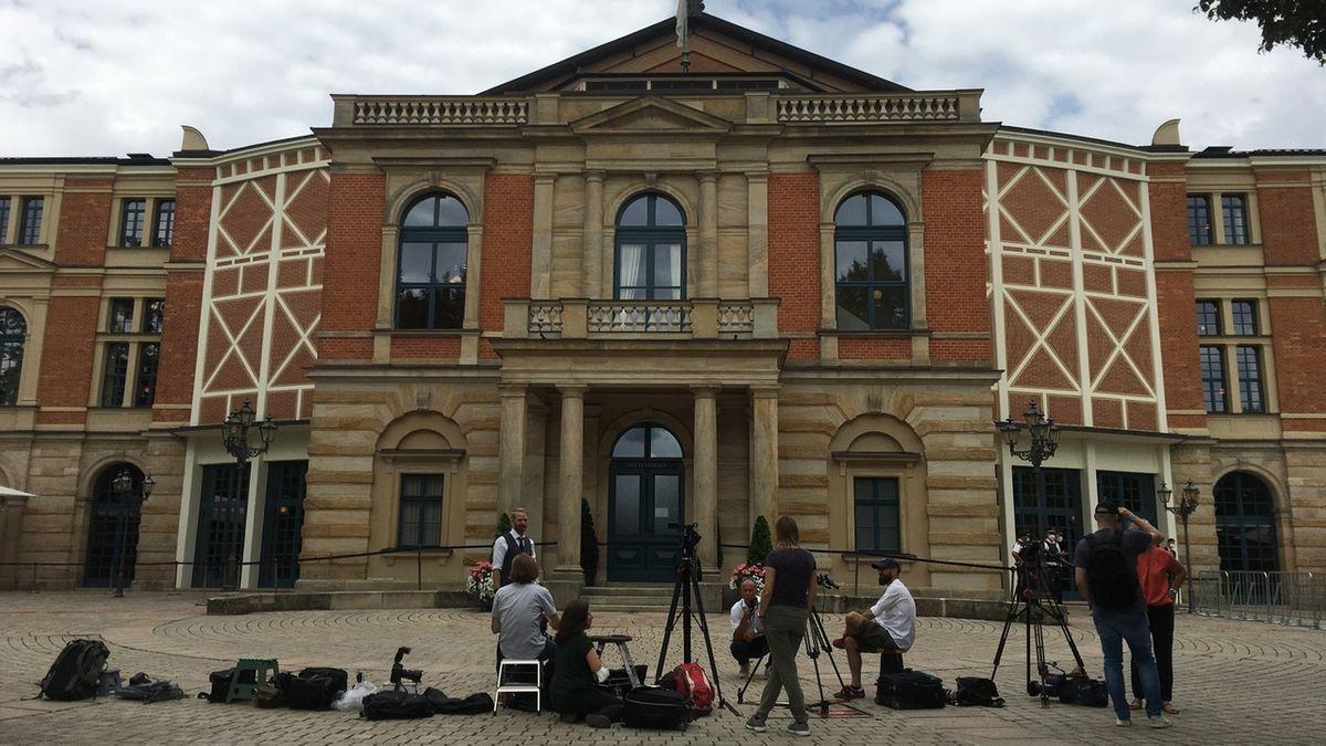 Kameraleute und Journalisten mit ihrem Equipment warten vor dem Festspielhaus, vor dem sie Stative, Kamera und Mikrophone aufgebaut haben.