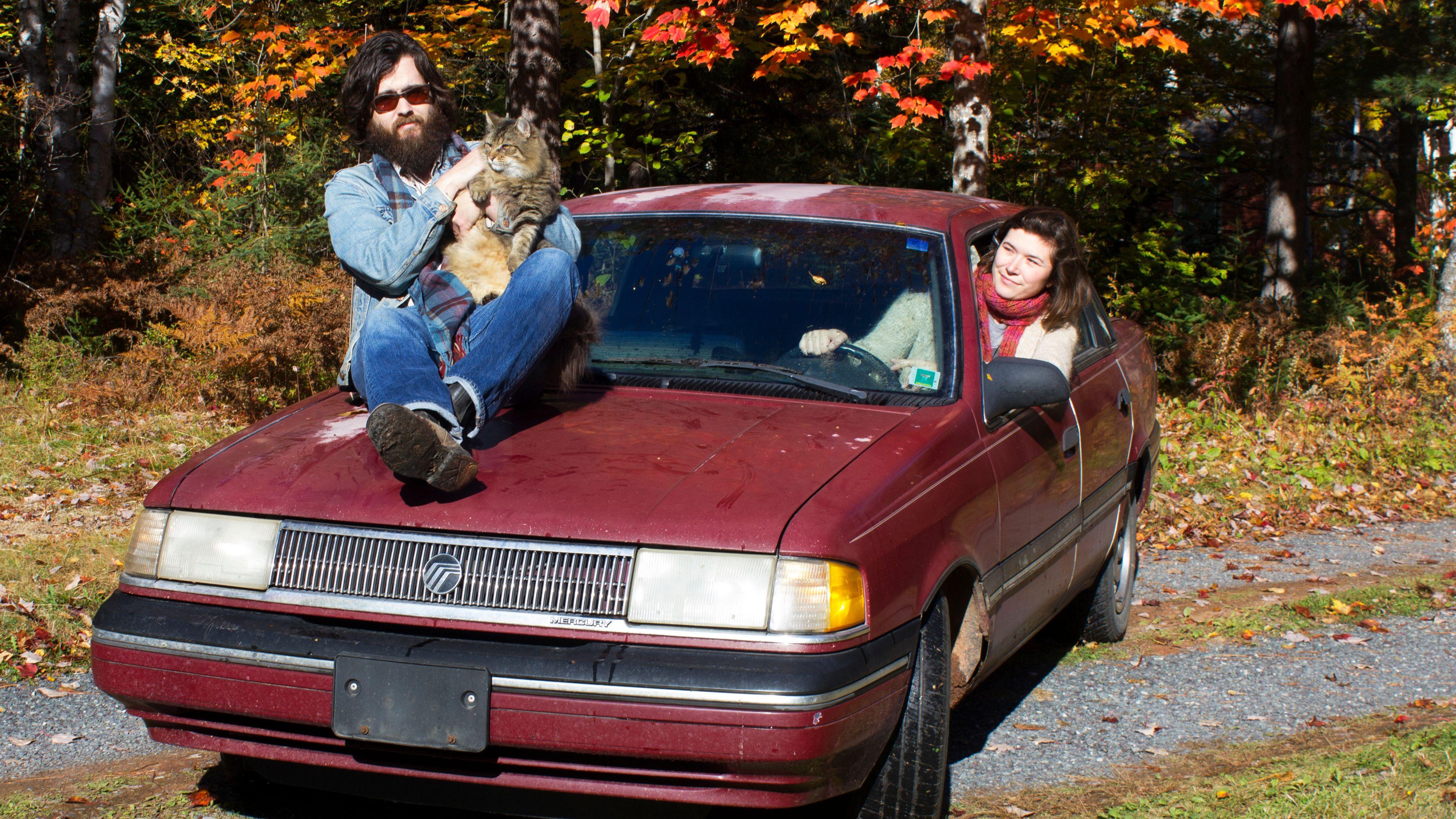 Ein Mann sitzt auf der Motorhaube eines roten Autos, an dessen Steuer eine Frau sitzt. Er hält eine Katze auf dem Arm.