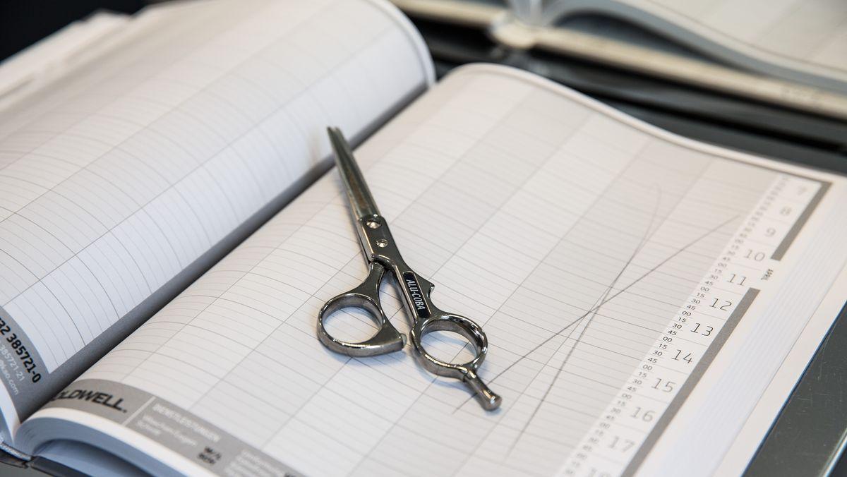 Friseurschere auf einem leeren Terminkalender eines Friseurgeschäftes (Symbolbild)