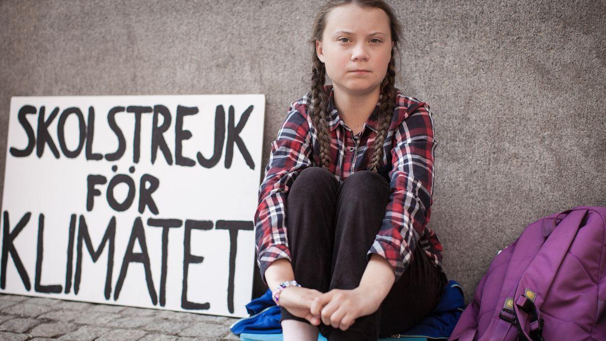 """Greta Thunberg sitzt auf der Straße, neben sich ein Protestschild mit der Aufschrift """"Skolstrejk för Klimatet"""" (Filmszene aus """"I am Greta"""")."""