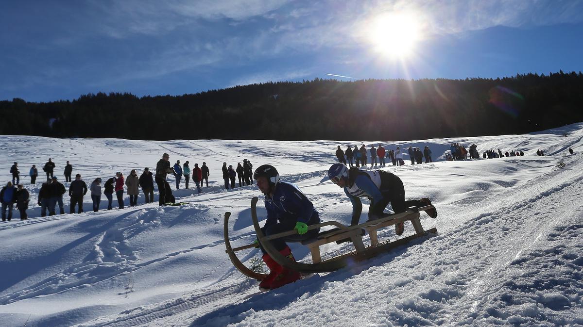 Ein Zweierteam vor Zuschauern auf der Piste des Schlittenrennens in Bad Hindelang im Oberallgäu