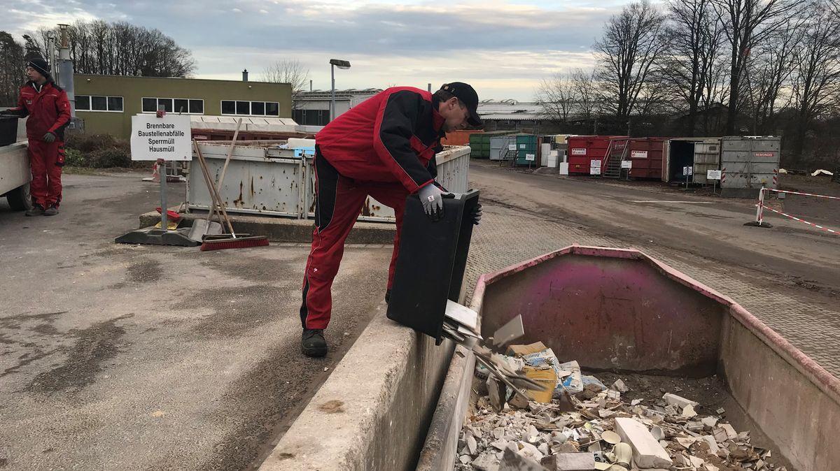Landwirt Matthias Ullmer kippt Fliesen aus einer Plastikwanne auf einem Wertstoffhof in einen Container.
