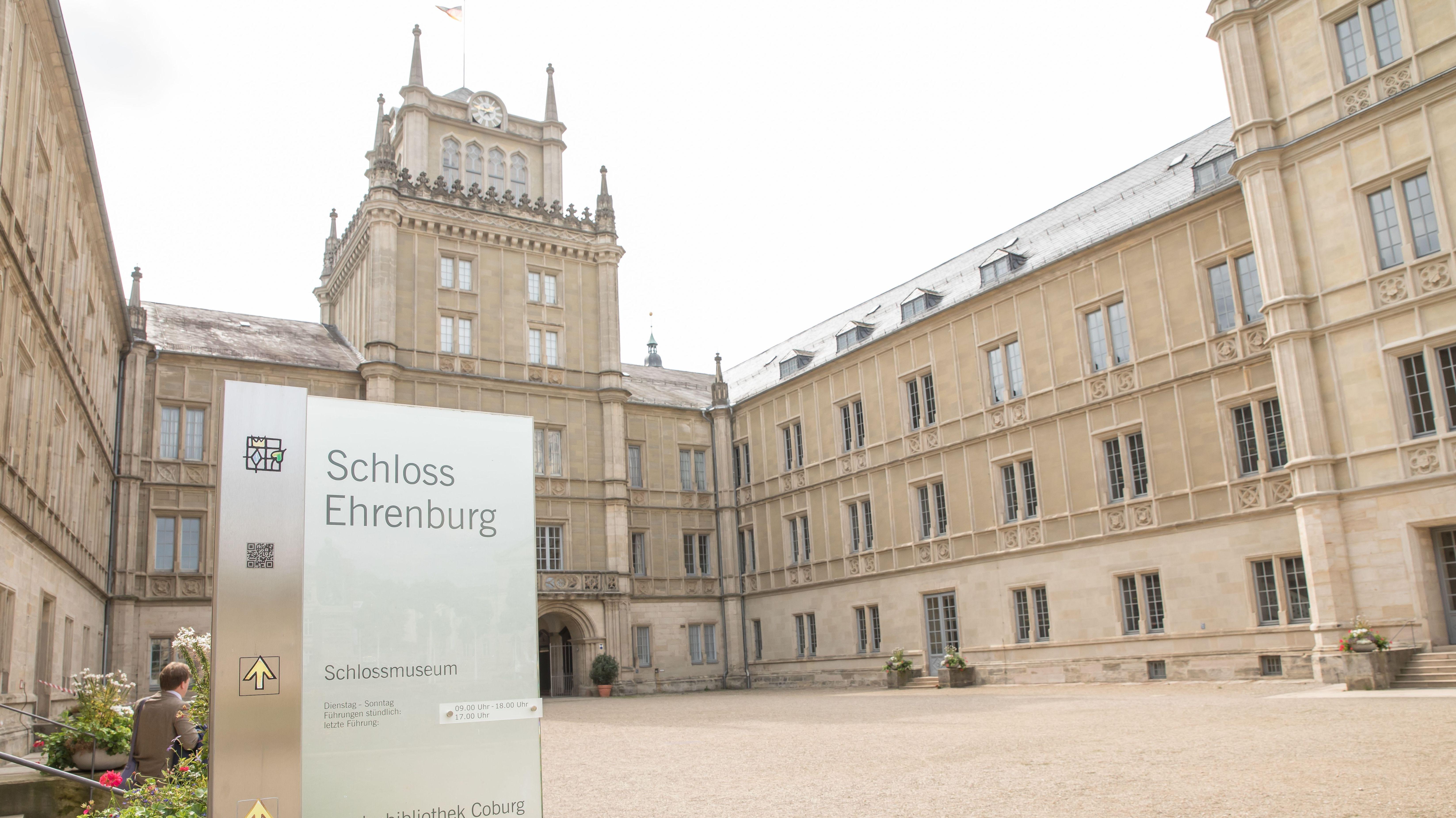 """Ein Schild mit der Aufschrift """"Schloss Ehrenburg"""" mit dem Schloss im Hintergrund"""