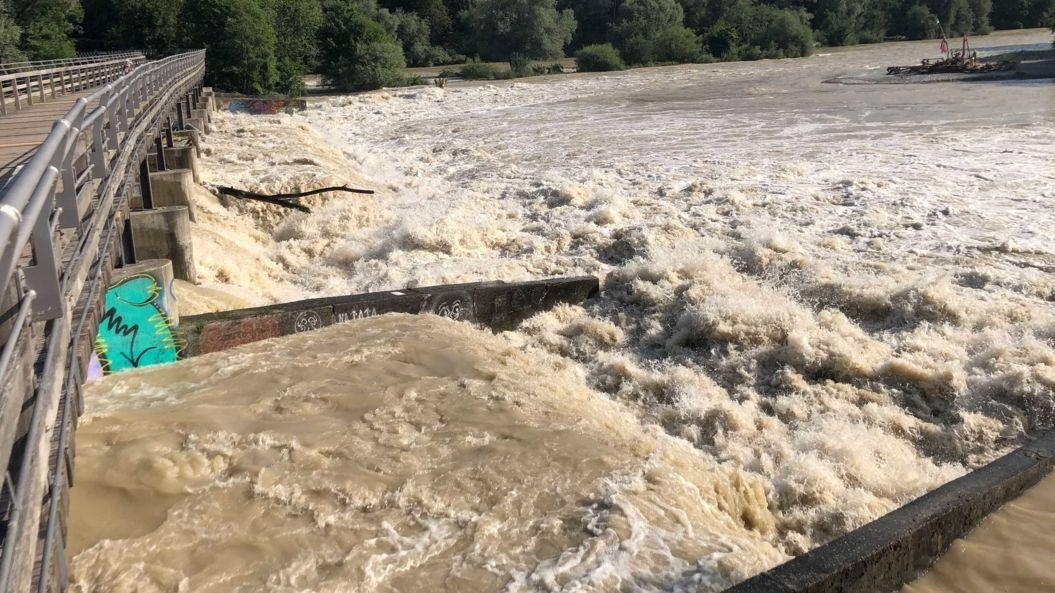 Braunes Wasser strömt die Isar hinunter, die auch Hochwasser führt.