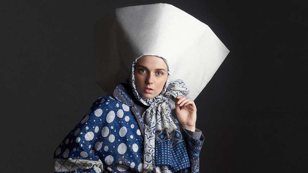 Frau mit großem Hut und blau-weißem Kleid