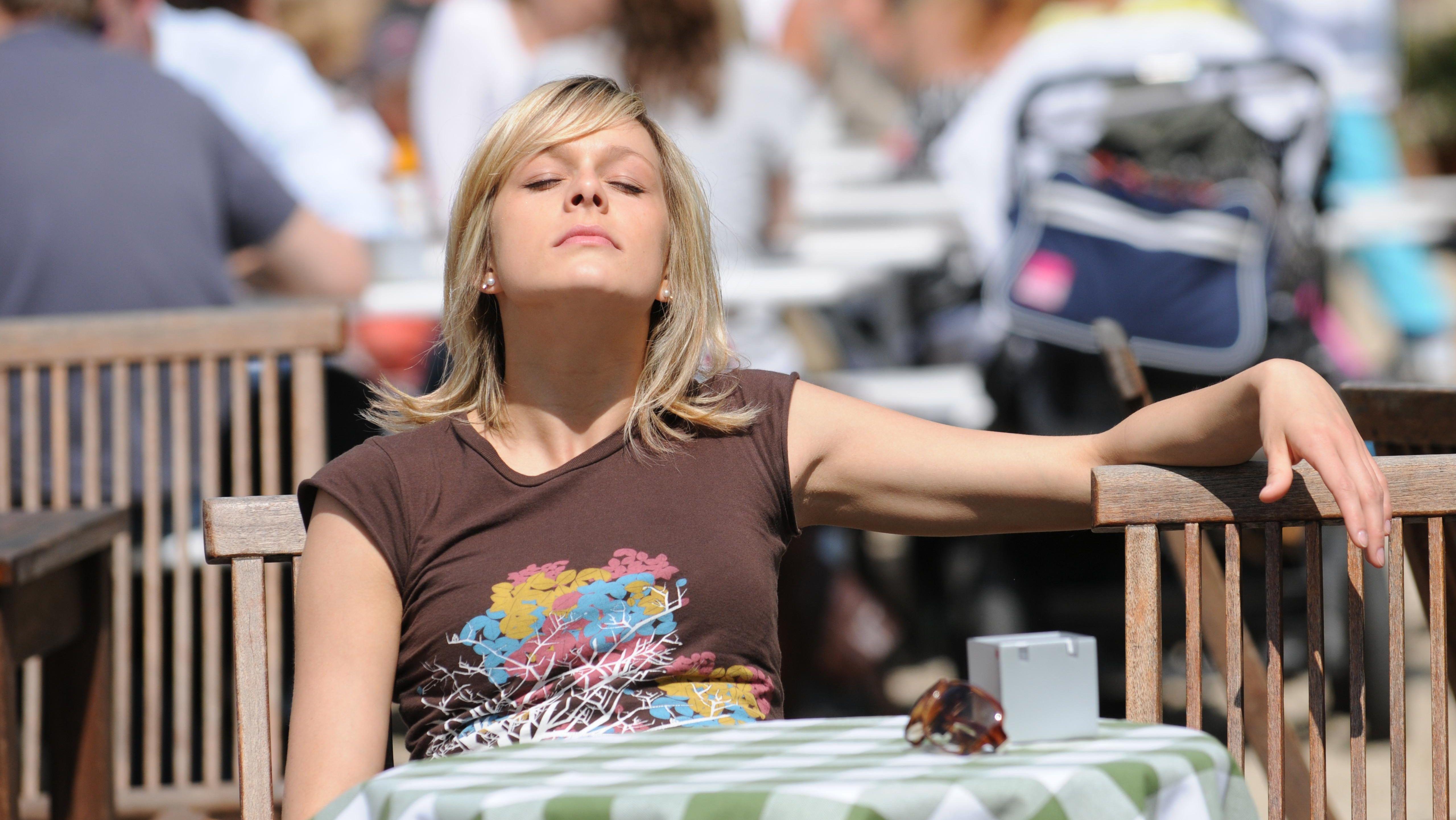 Junge blonde Frau sitzt in einem Café im Sonnenschein, sonnt sich, entspannt.