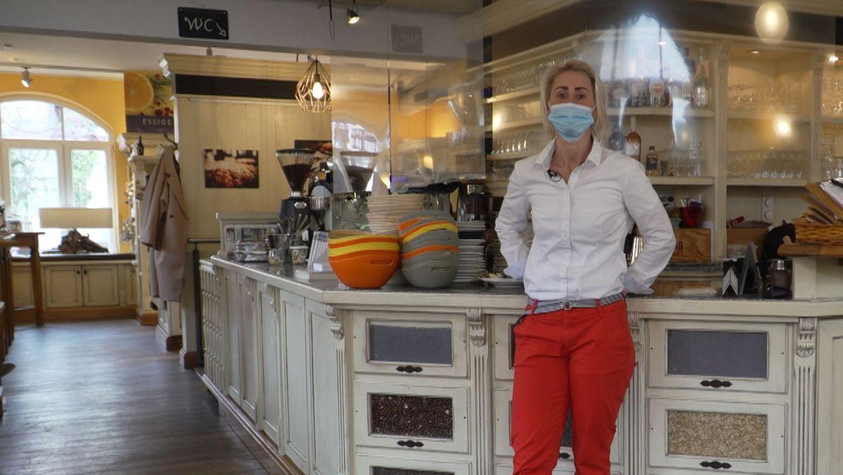 Jana steht mit Mundschutz am Tresen in ihrem Café in Aschheim.