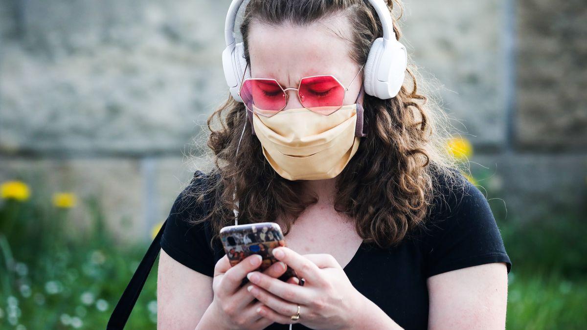 Frau mit Handy und Schutzmaske
