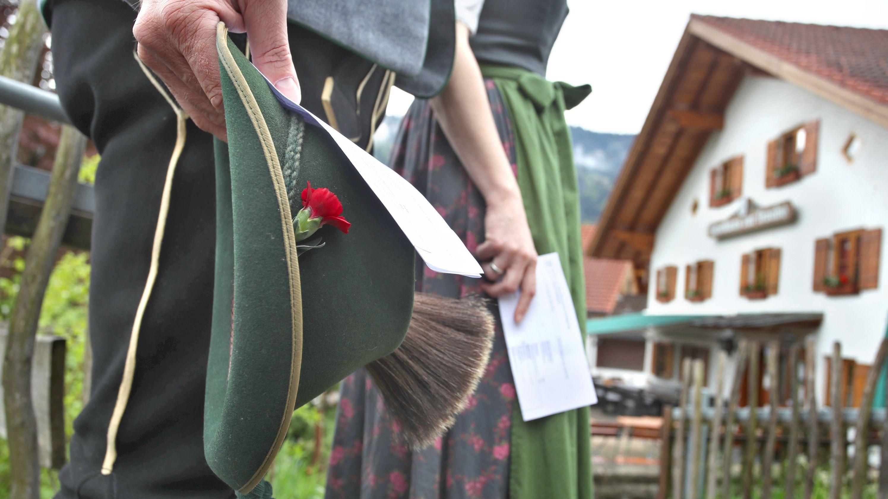 Ein Paar in Allgäuer Tracht, mit ihren Wahlbenachrichtigungen in Händen auf dem Weg zum Wahllokal.