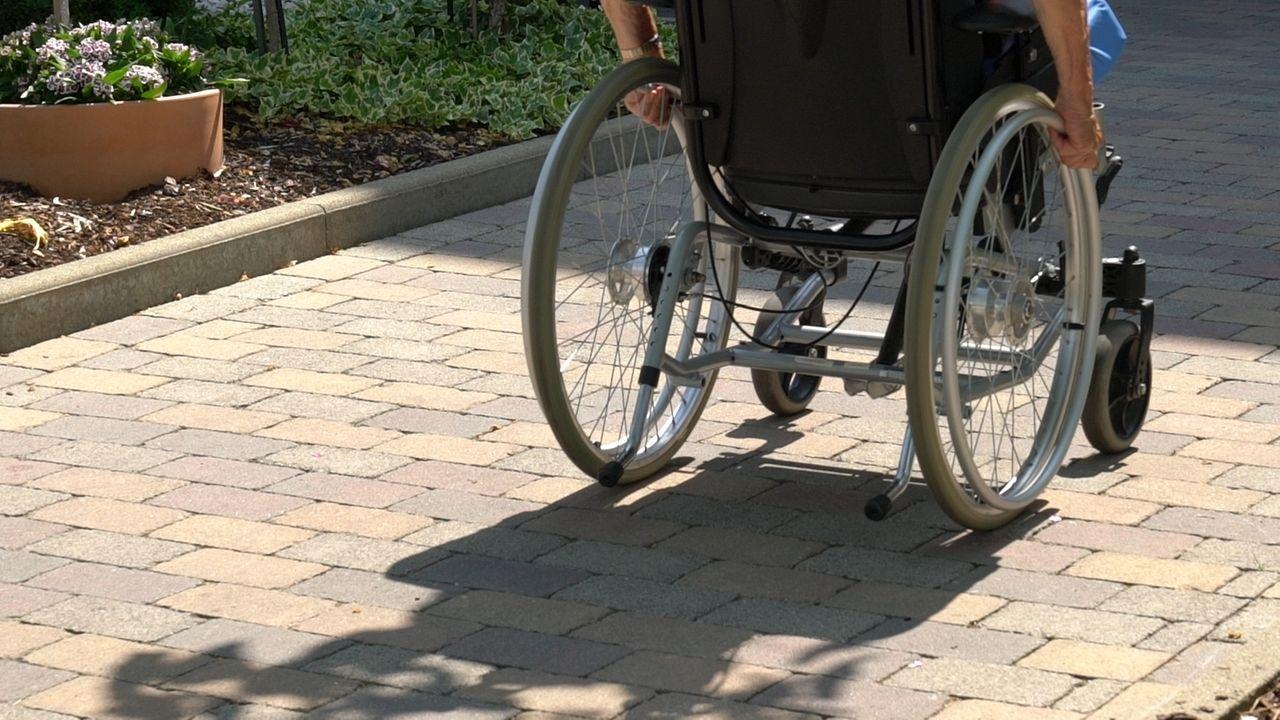 Rollstuhlfahrerin fährt auf einem Weg