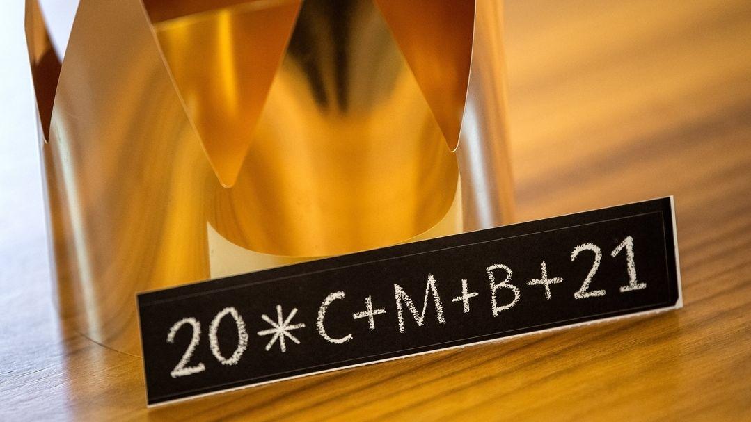 """Ein Aufkleber mit der Aufschrift """"20*C+M+B+21"""" liegt neben einer Krone."""