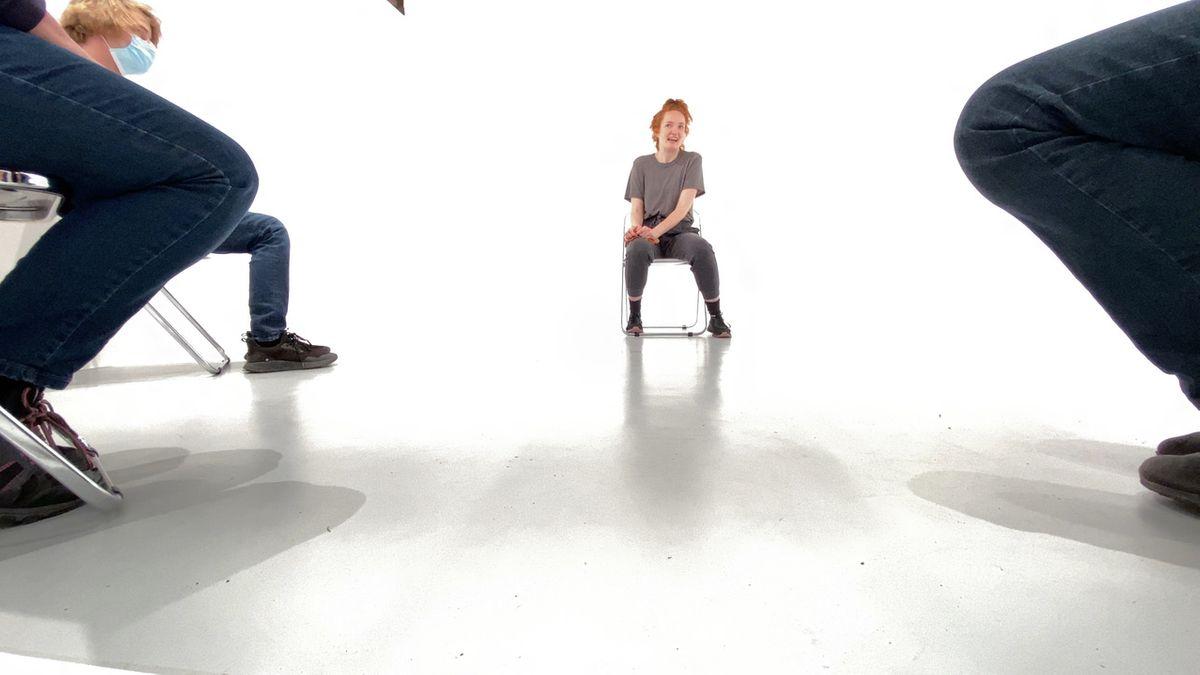 Frau sitzt vor weißem Hintergrund auf einem Stuhl, vorne sitzen weitere Personen.