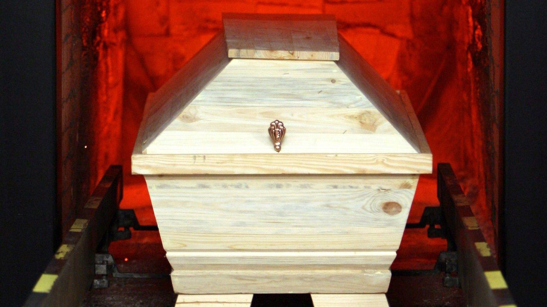 Ein Sarg wird in einem Krematorium zur Feuerbestattung in einen Ofen gefahren.