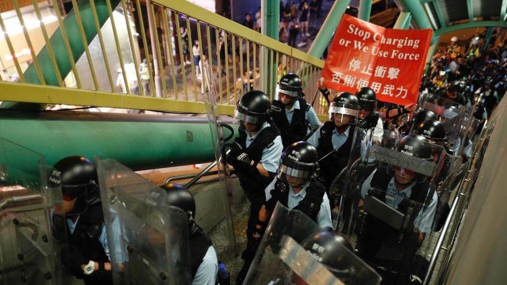 """Polizisten in Hongkong bereiten sich auf die Begegnung mit Demonstranten vor und halten ein Plakat mit der Aufschrift """"Stoppt die Aktionen, sonst gebrauchen wir Gewalt"""""""