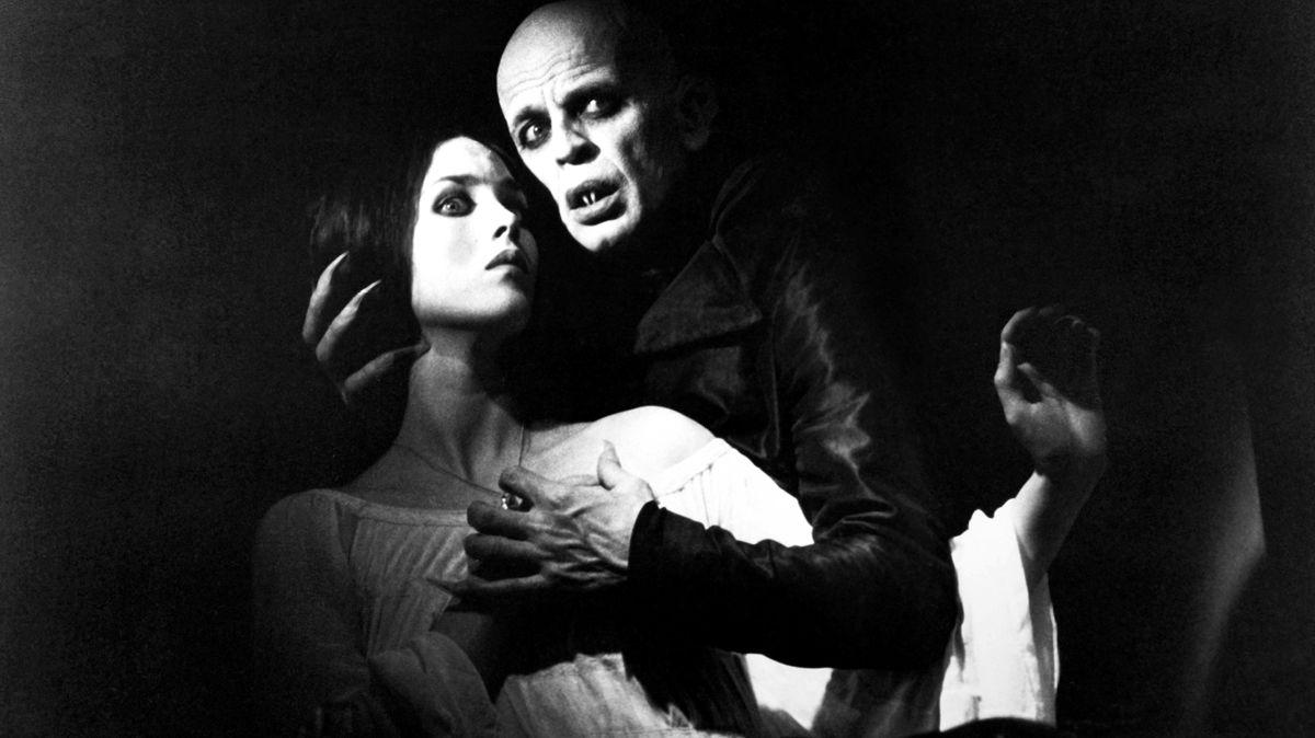 Still aus dem Film Nosferatu: Der Vampir ist über eine junge Frau gebeugt.
