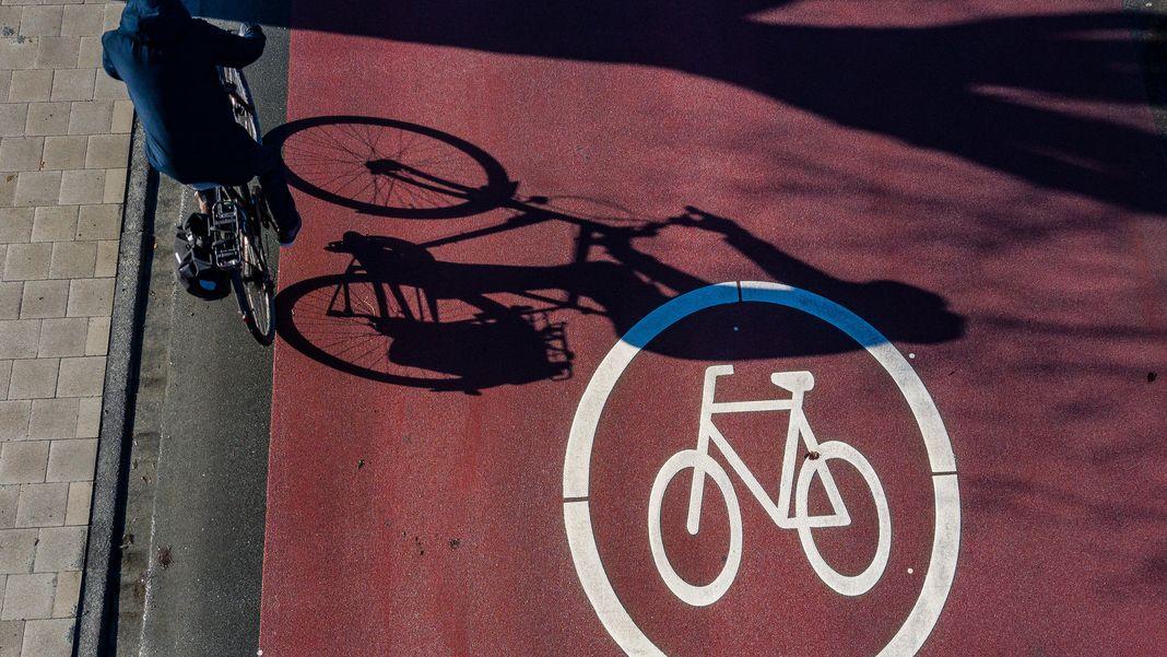Ein Radfahrer wirft auf einer Fahrradstraße seinen Schatten auf die Fahrbahn.