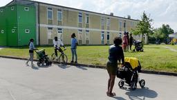 Im Transitzentrum für Asylsuchende in Manching unterhalten sich Männer und Frauen vor einem Wohngebäude.   Bild:picture-alliance/dpa