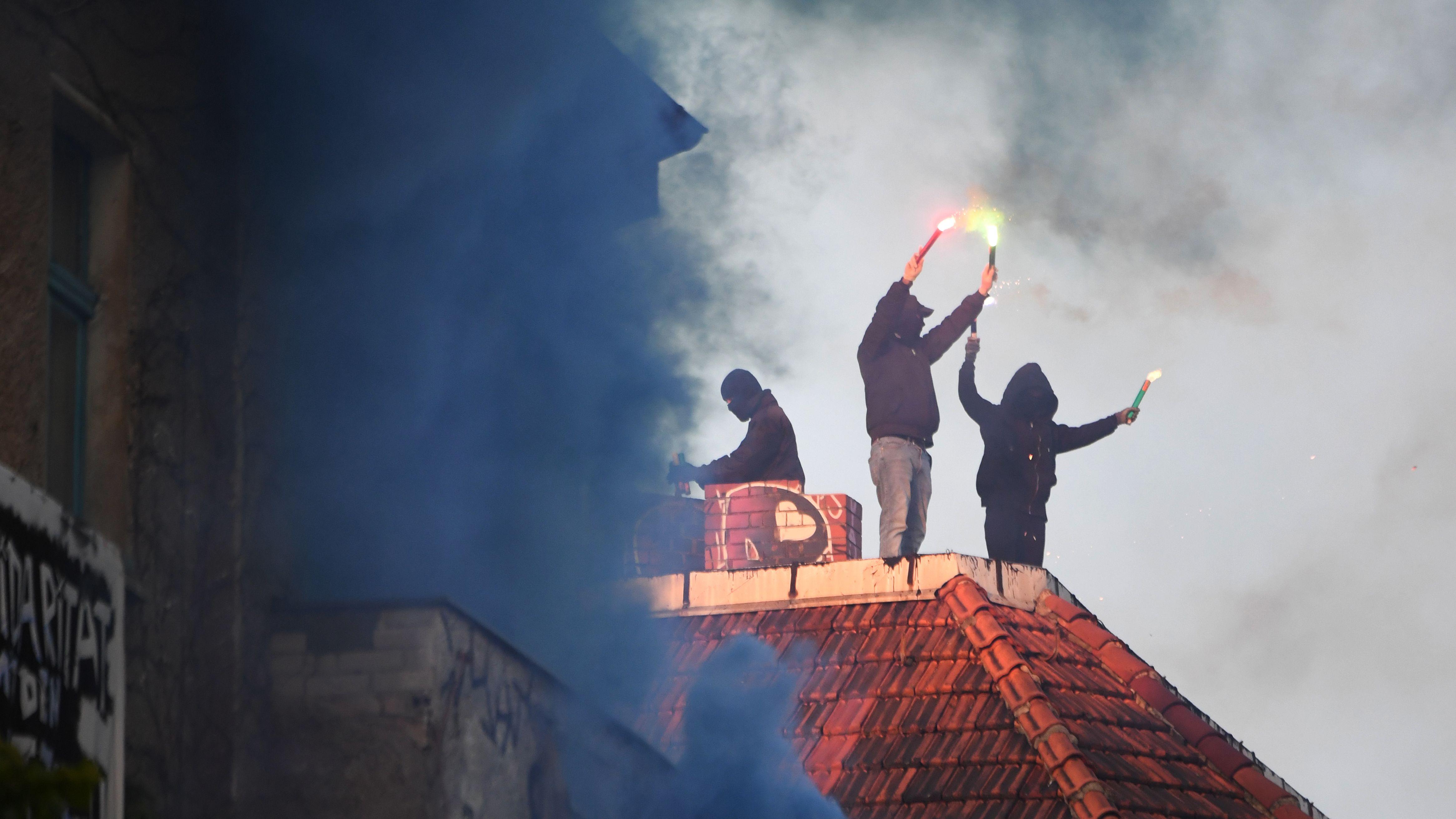 Archivbild: Unterstützer der linksradikalen «Revolutionären 1. Mai-Demonstration» stehen mit Pyrotechnik in den Händen auf einem Dach in Friedrichshain.