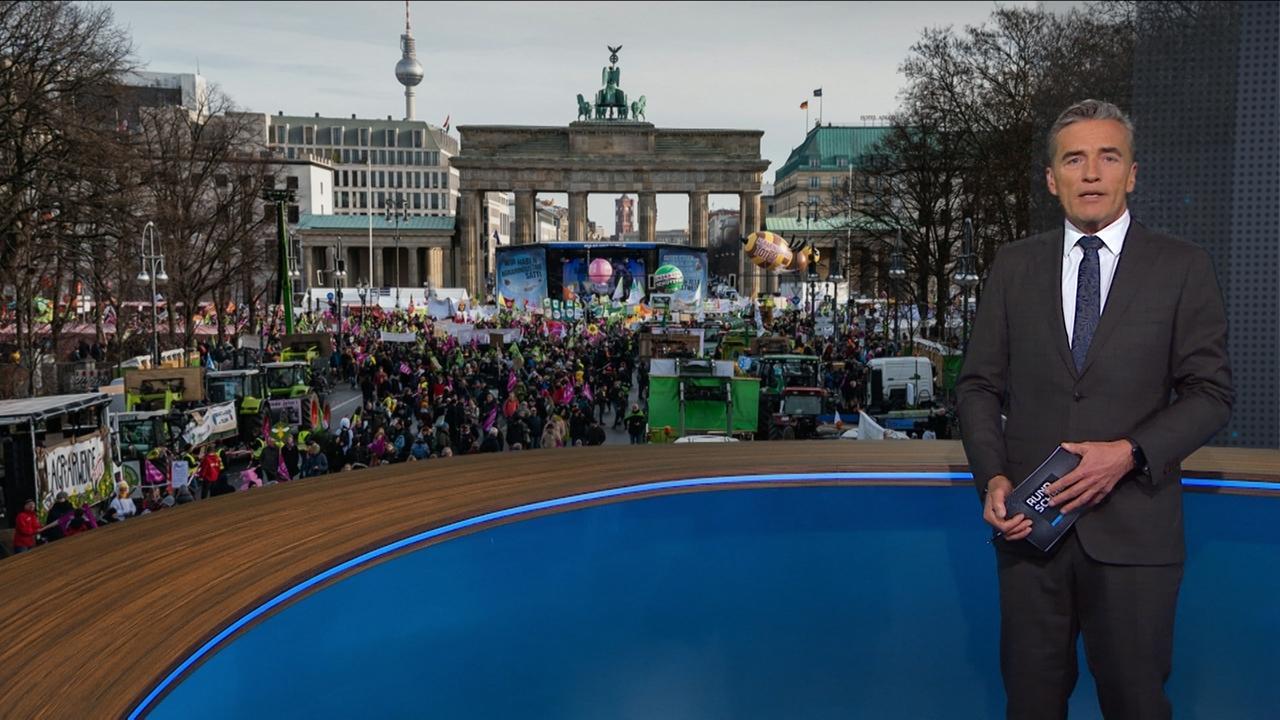 Moderator Stefan Scheider vor einem Bild der Demonstration für eine Agrarwende