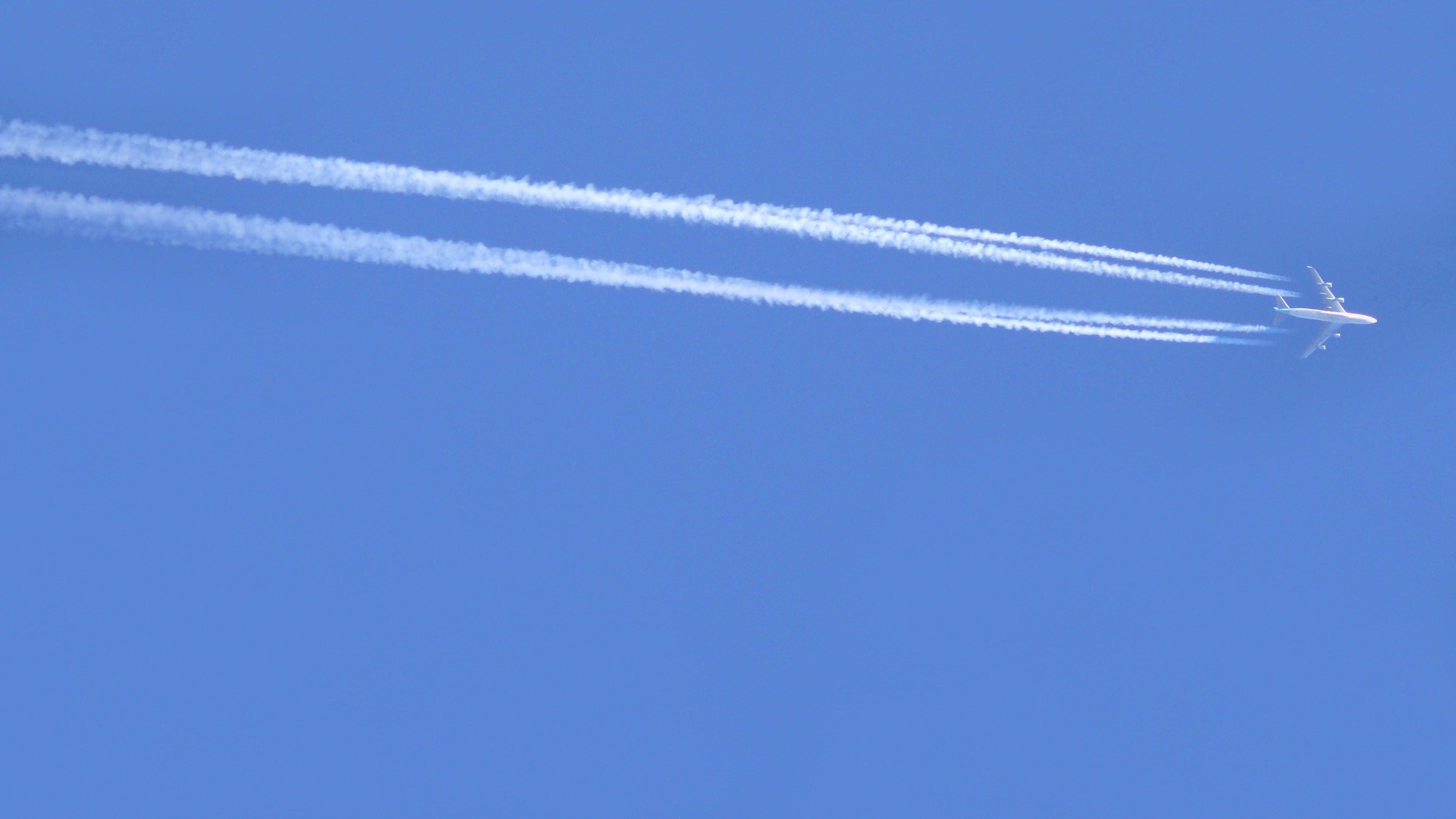 Flugzeug am Himmel mit Kondensstreifen
