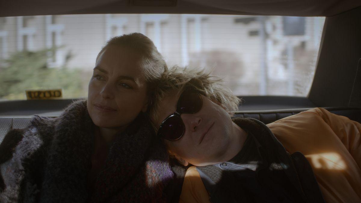 """Eine Frau und ein Mann sitzen aneinandergelehnt auf der Rückbank eines Taxis. Szene aus dem Film """"Schwesterlein""""."""