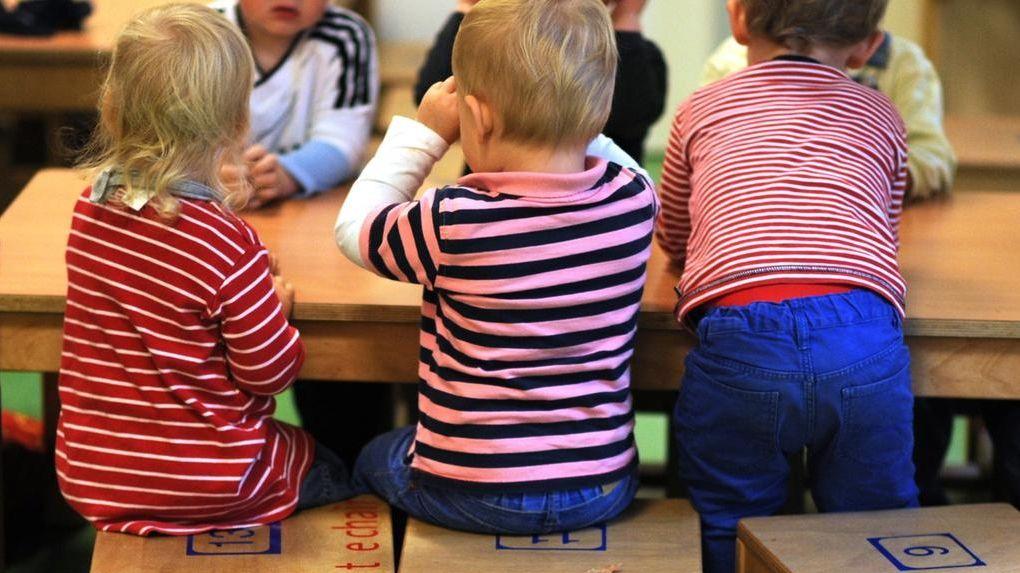 Kinder sind von hinten zu sehen, wie sie nebeneinander in einer Kita sitzen.