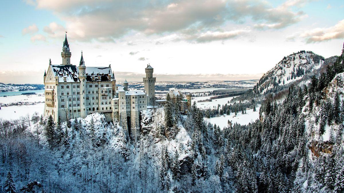 Inmitten der winterlichen Landschaft steht das Schloss Neuschwanstein bei Hohenschwangau (Bayern).