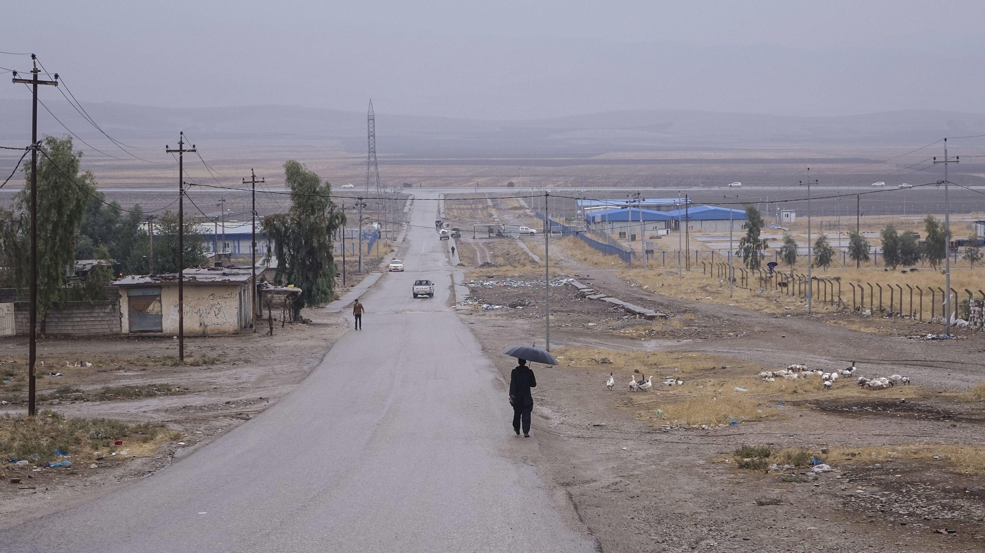 Eine Straße im Nordirak führt an einem Flüchtlingscamp im Nordirak vorbei - man sieht vereinzelte Autos, Menschen und Tiere in der tristen Umgebung