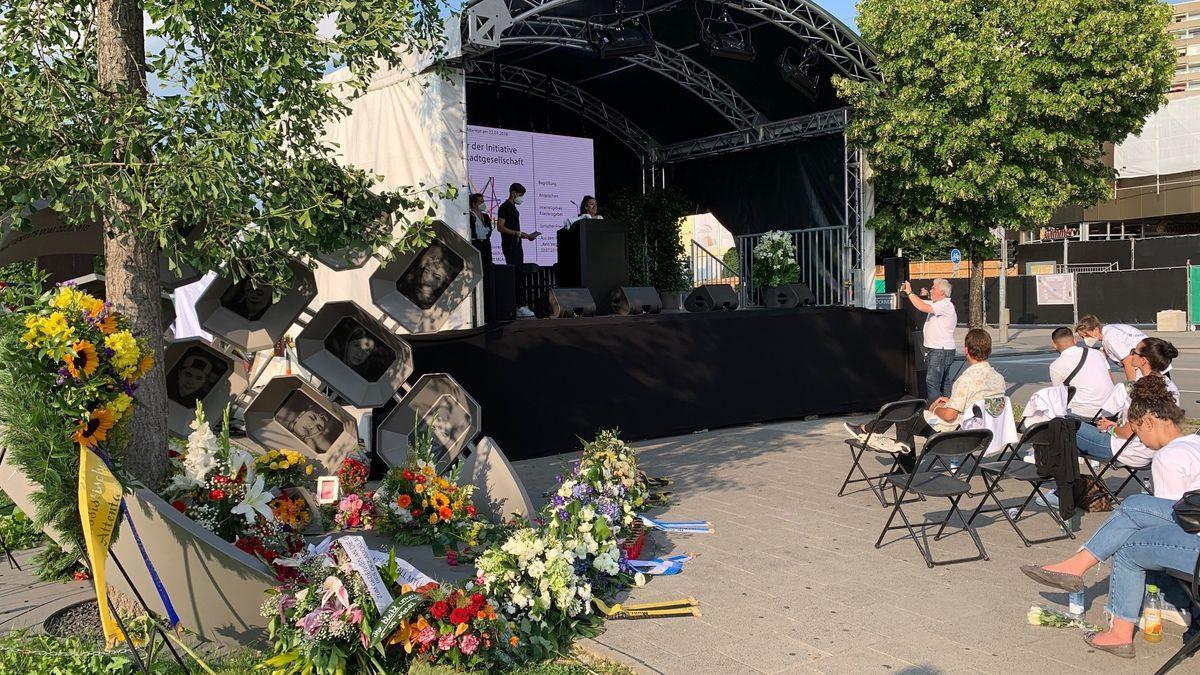 Links im Vordergrund das mit Blumen geschmückte Mahnmal für die Opfer des Anschlags am OEZ, im Hintergrund die Bühne für die Gedenkveranstaltung, rechts im Vordergrund die Teilnehmerinnen und Teilnehmer der Veranstaltung.