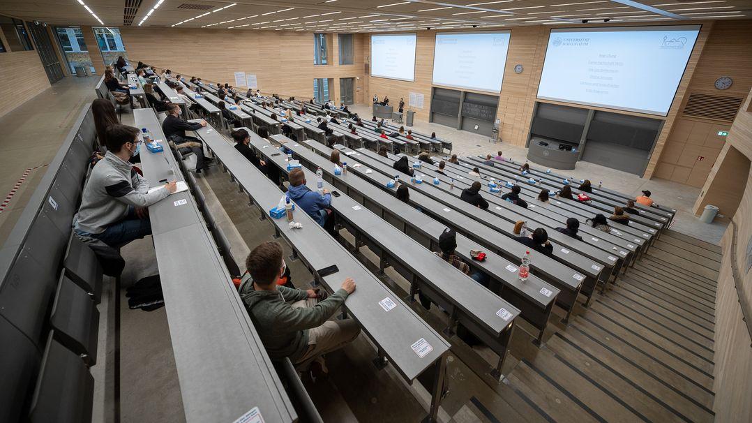 Studierende mit Mund- und Nasenmaske sitzen in einem Hörsaal der Universität Hohenheim.