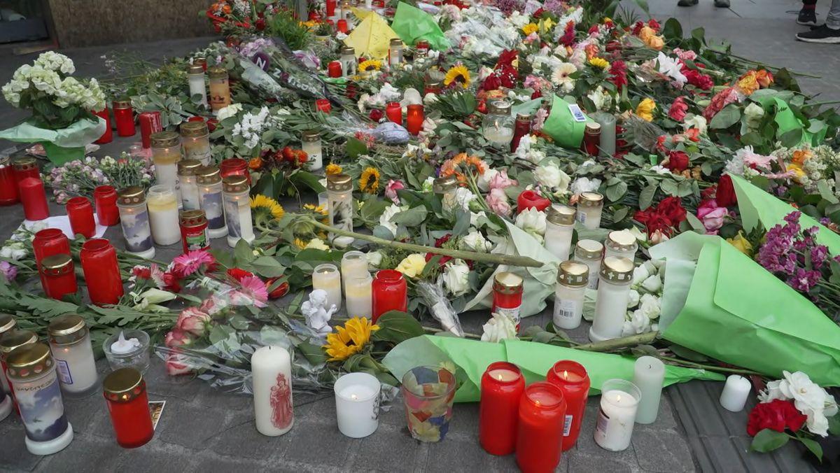 Grablichter, Kerzen und Blumen liegen vor einem Kaufhaus in der Würzburger Innenstadt.