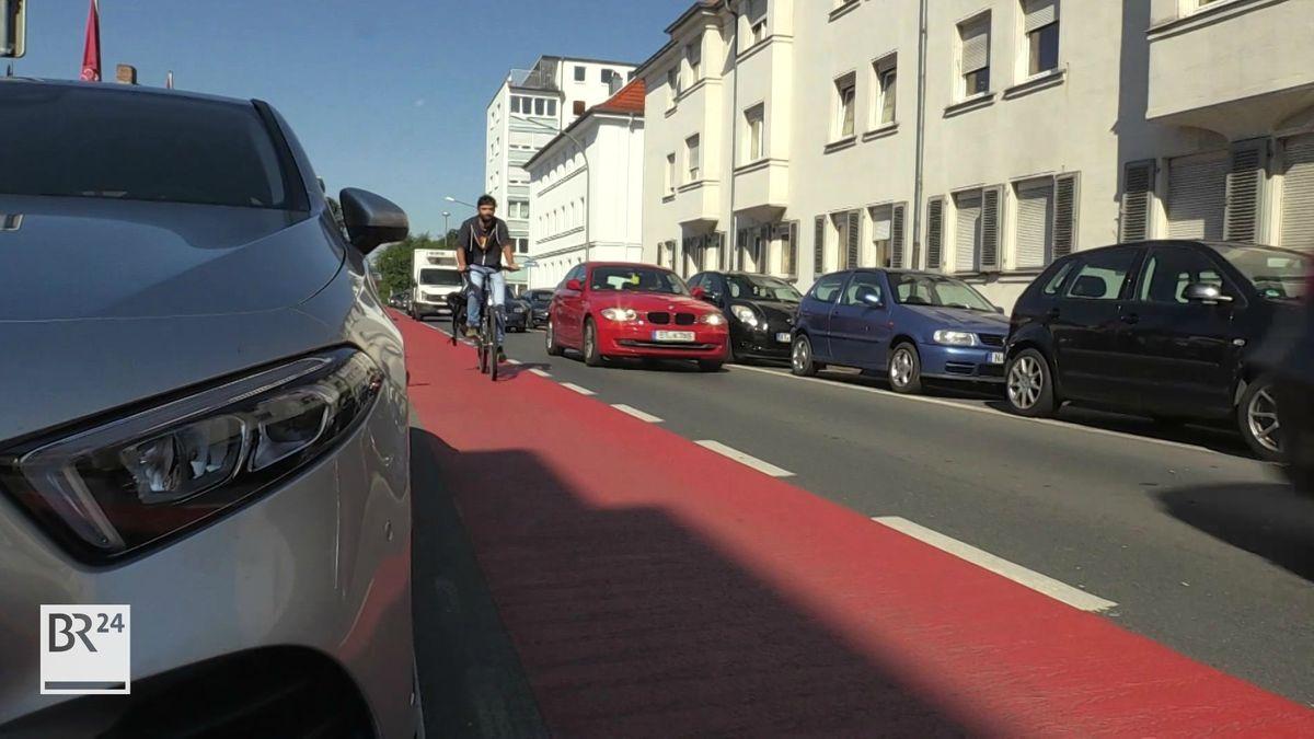 Auf einem leuchtend roten Radweg fährt ein Radfahrer mit Lastenanhänger, rechts und links von ihm sind Autos unterwegs.