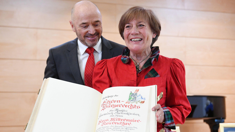 Rosi Mittermaier hält das Goldene Buch der Marktgemeinde Garmisch-Partenkirchen, Christian Neureuther steht neben ihr.