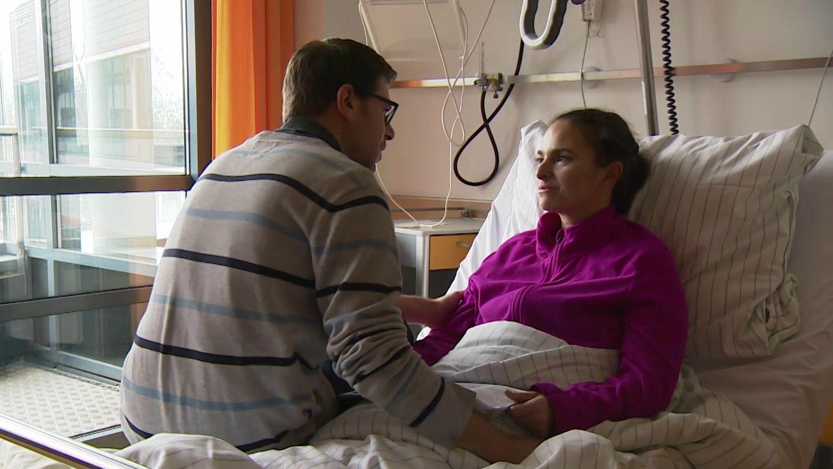 Jasmin Sen-Kunoth liegt im Krankenhausbett, ihr Mann sitzt ihr gegenüber und hält ihre Hand