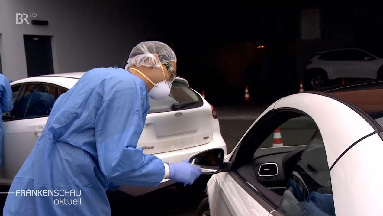 Ein medizinischer Mitarbeiter in blauer Schutzkleidung und Mundschutz nimmt einen Abstrich von einer Person, die im Auto sitzt.