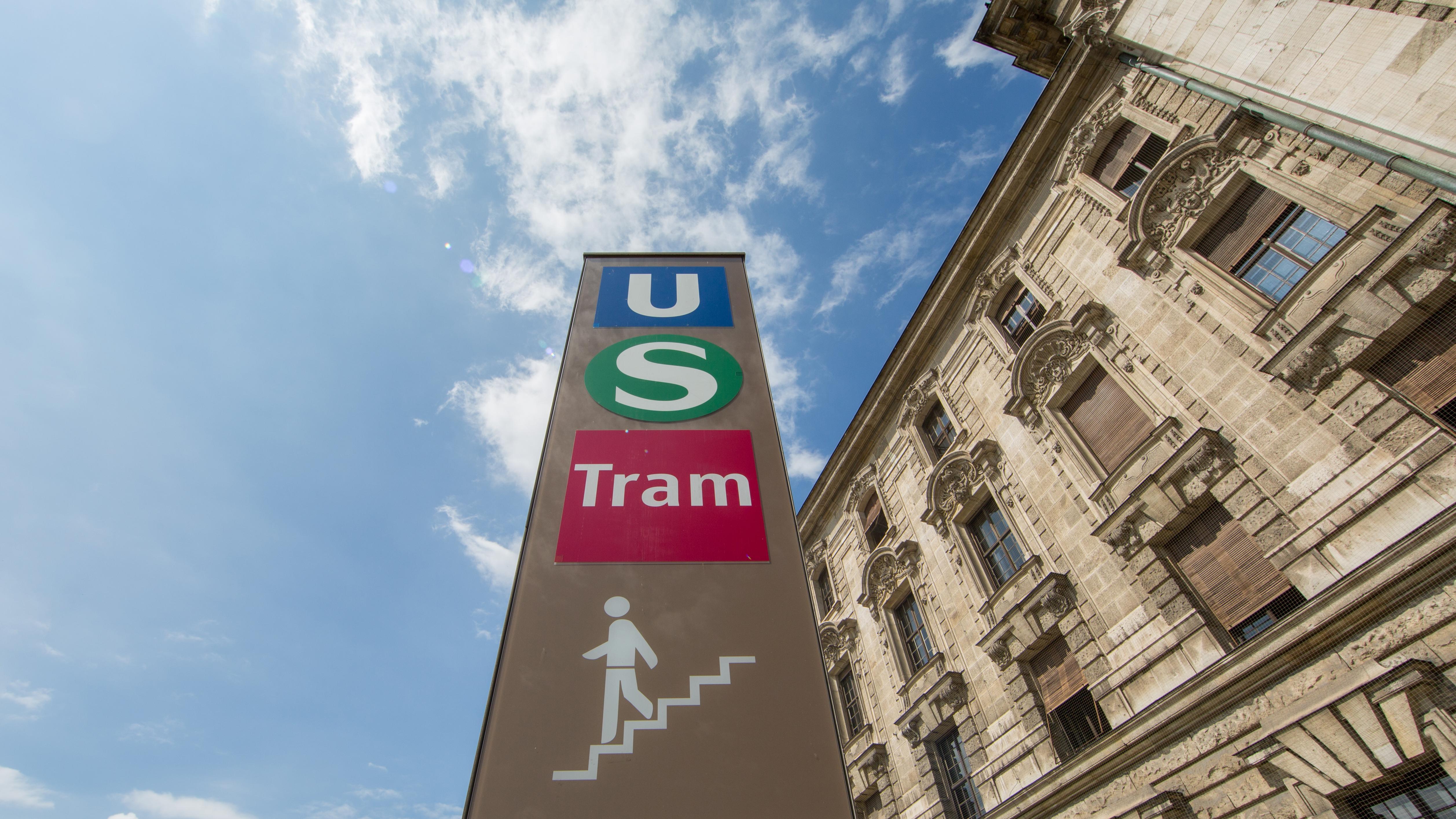 Hinweisstele mit U-Bahn-, S-Bahn- und Tram-Logo vor dem Münchner Justizpalast.