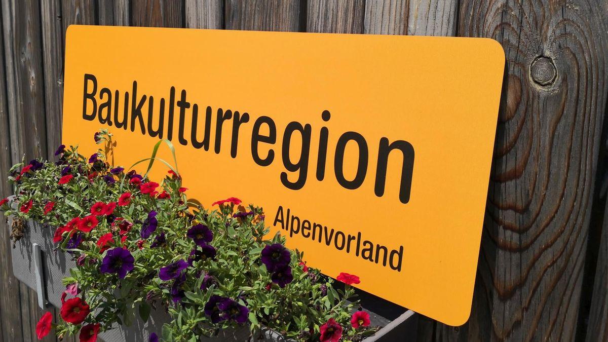Ein oranges Schild, darauf steht: Baukulturregion Alpenvorland.