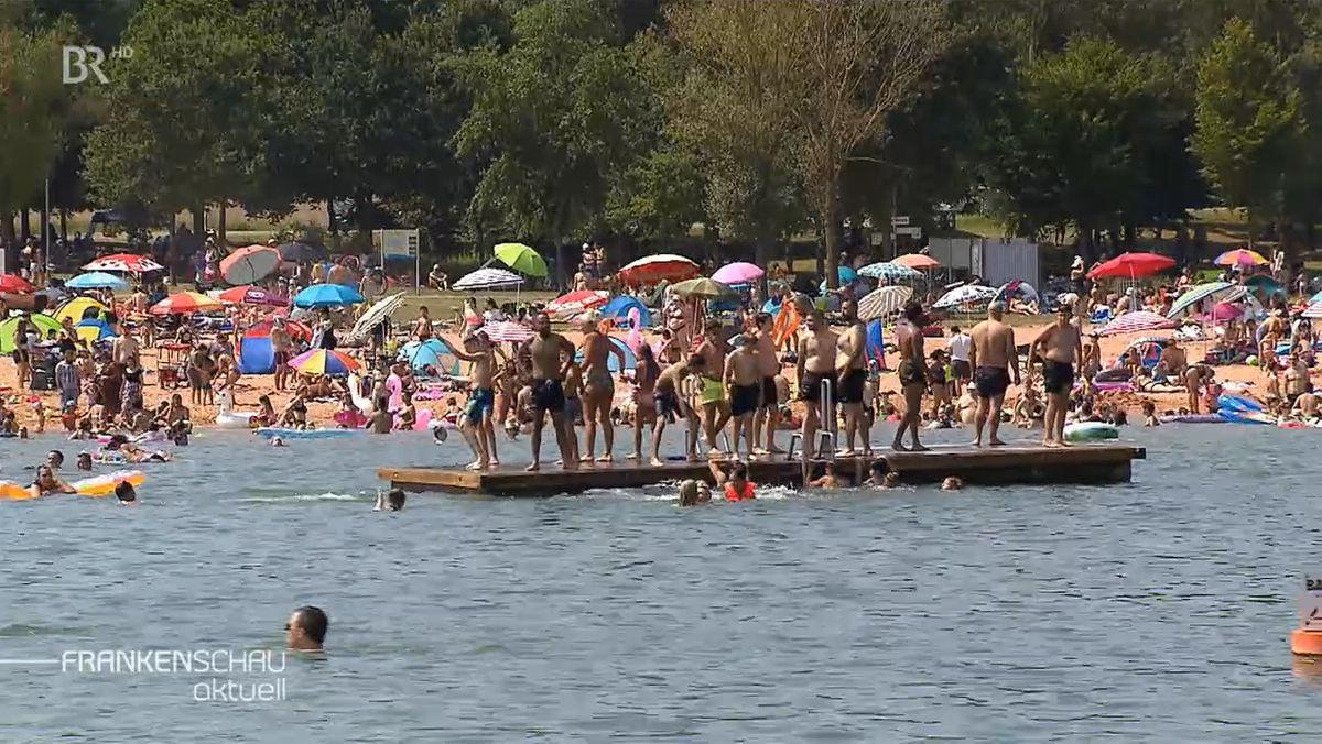 Viele Menschen in Badekleidung halten sich am Ufer eines Badesees auf, einige stehen auf einem Holzfloß, einige schwimmen.