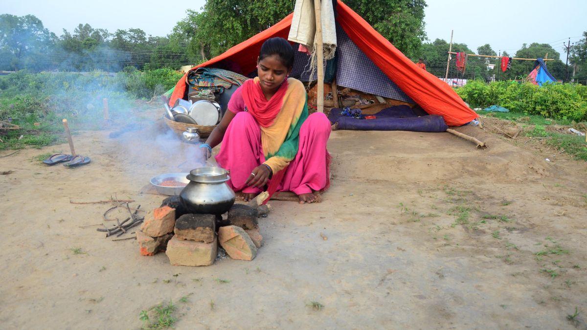 Ein junges Mädchen kocht vor ihrer einfachen Unterkunft im indischen Allahabad.