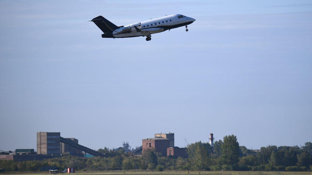 Flugzeug über Rollfeld und Ortschaft.