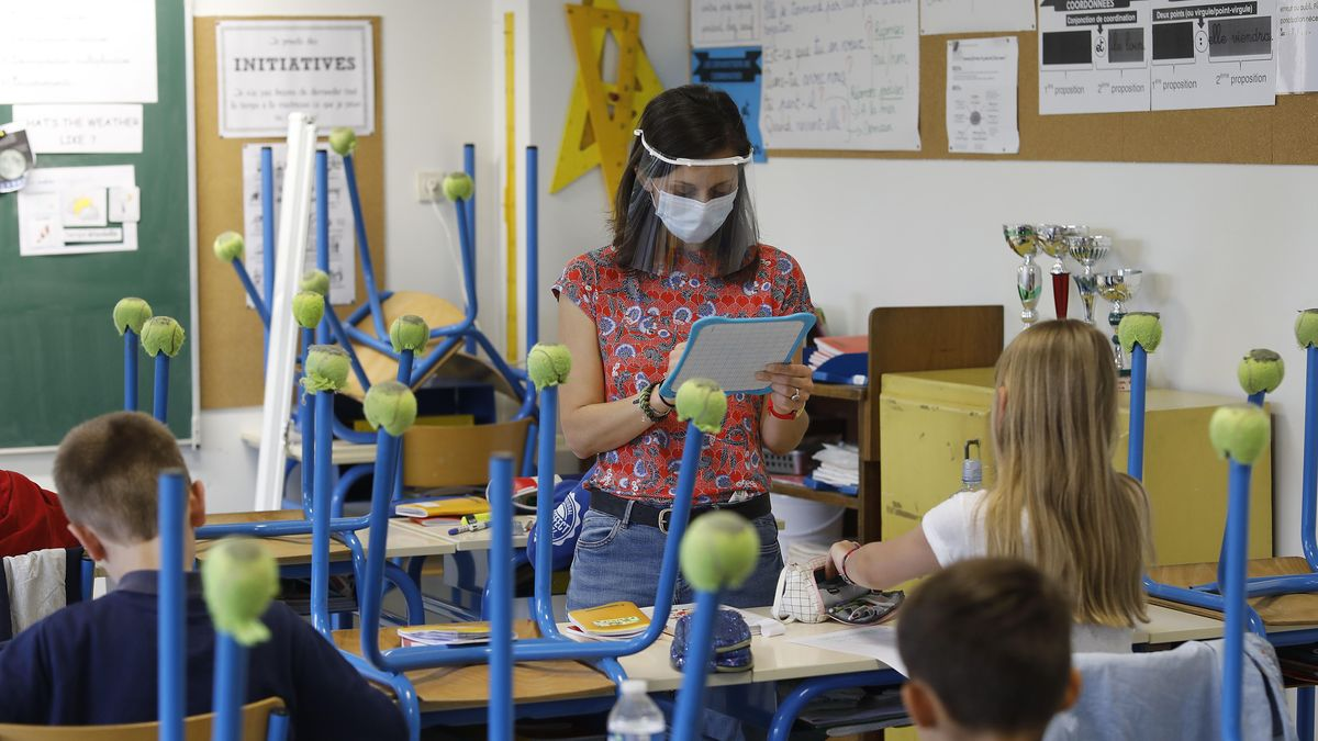 Lehrerin mit Mundschutz steht vor einer Klasse