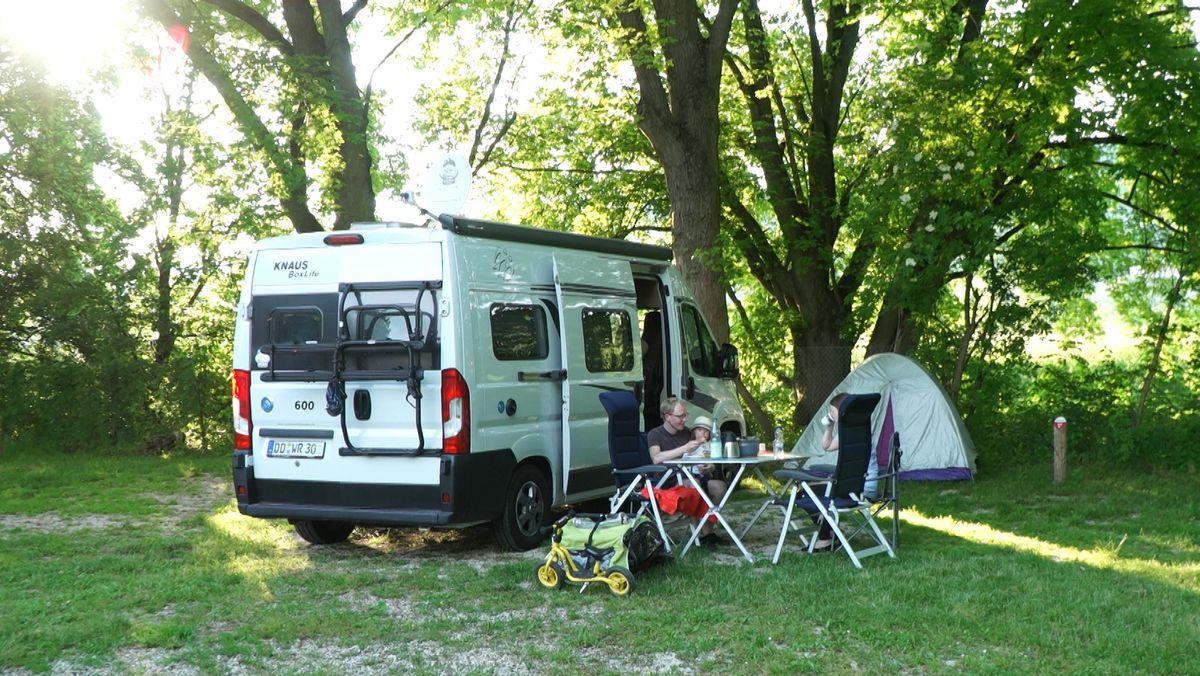Ein Campervan und eine Familie auf einem Campingplatz