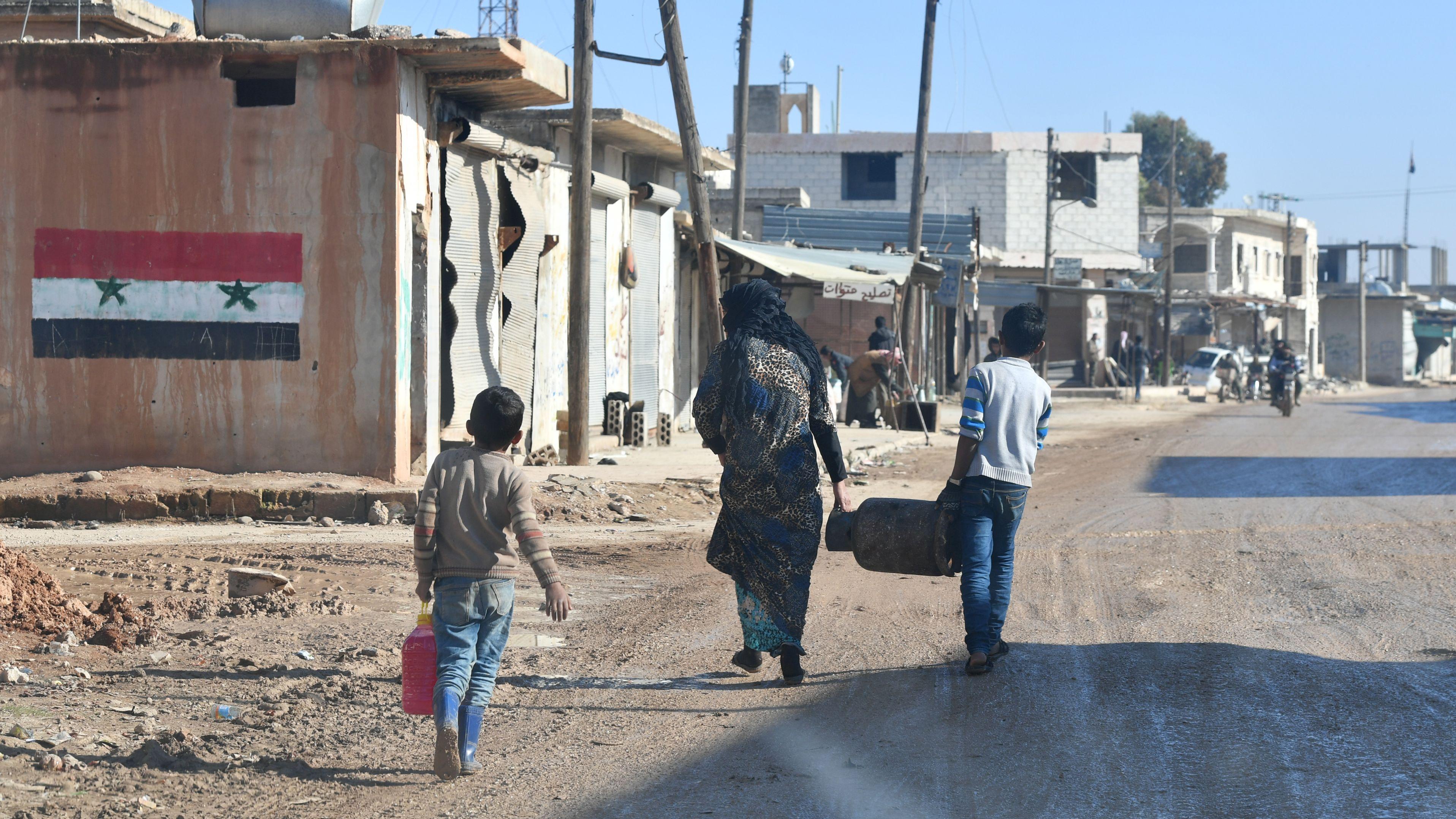 Ein Kind, eine Frau und ein größeres Kind gehen eine Straße entlang. Die Straße wird gesäumt von zerstörten Wohnhäusern. In der Ferne naht ein Motorrad.