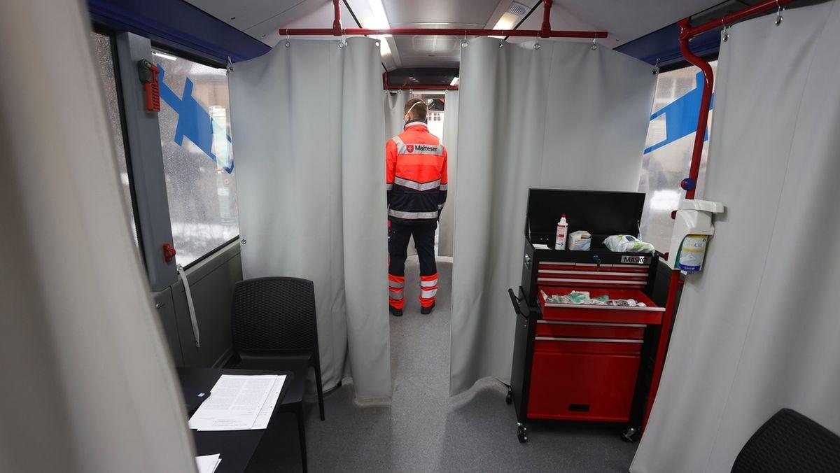 Am 28.01.2021 steht in Memmingen ein Mitarbeiter der Hilfsorganisation Malteser am städtischen Impfzentrum in einem Impfbus.
