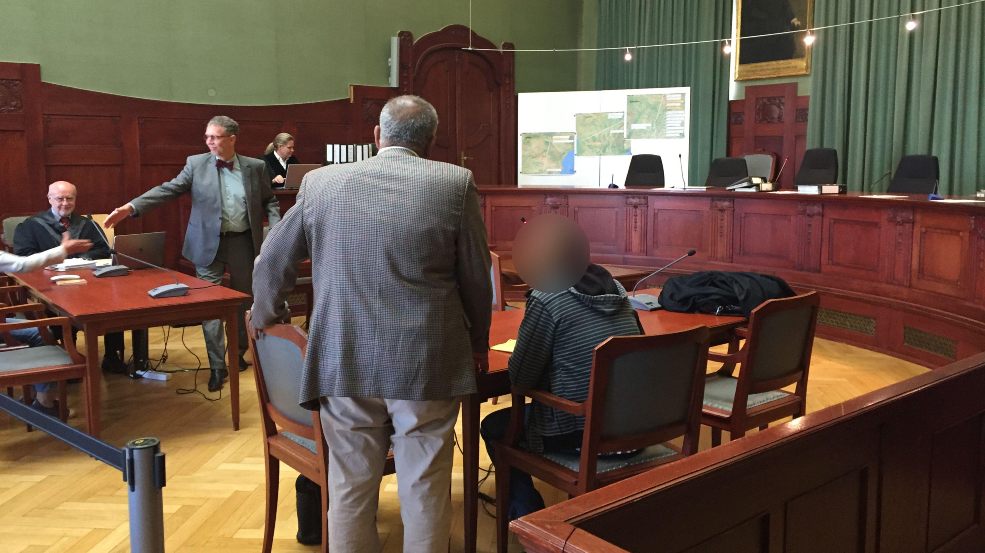 Blick in den Gerichtssaal im Bayreuther Landgericht - der Angeklagte sitzt an einem Tisch, neben ihm steht sein Übersetzer