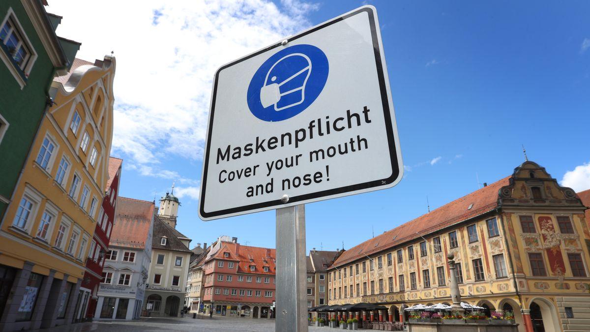 Auf einem Schild am Rathausplatz in Memmingen wird auf Maskenpflicht hingewiesen.