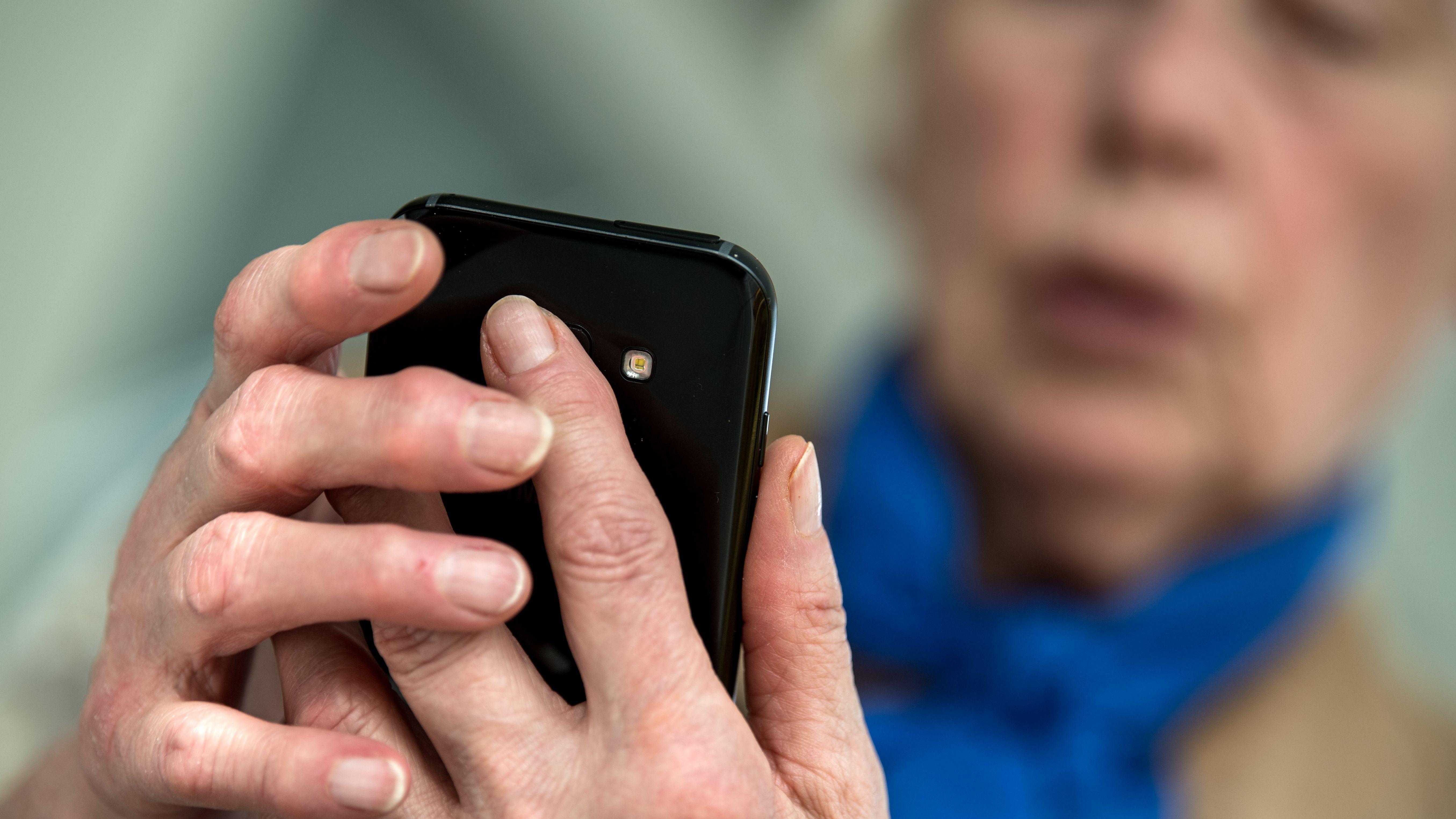 Eine Seniorin schaut auf ihr Smartphone - Symbolbild